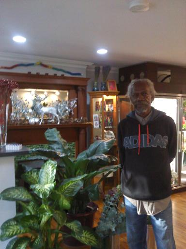 Harold King in his shop Flowergarden next to some of his beautiful houseplants.