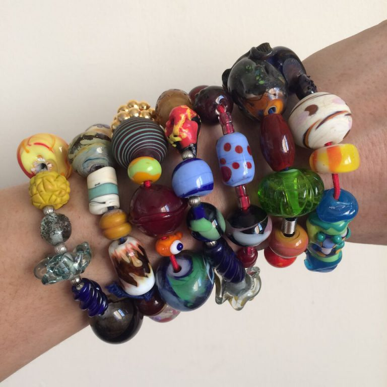 Community building: Instructor Amy Lemaire shows off four years of Bead Exchange Bracelets. Each bead was made by a different Bead Project Artist.