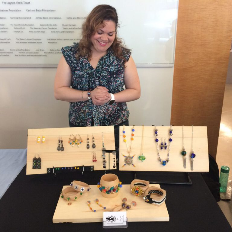 Bead Project alum Lilly Burgos showing off her jewelry line at the Bead Project Graduation Trunk Show in the Gallery at UrbanGlass. Photo credit: Amy Lemaire